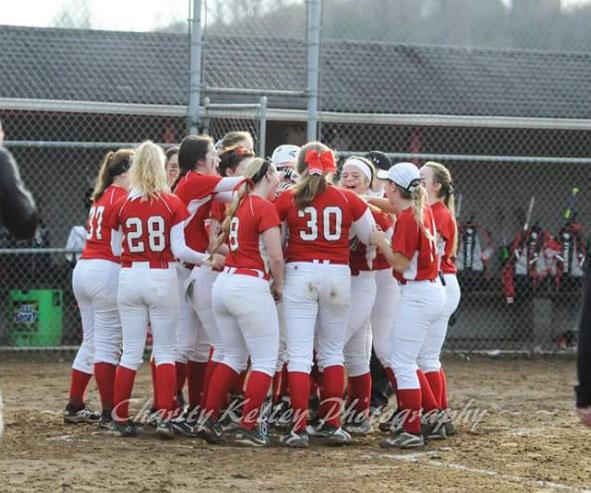 The team congratulates junior Ginny Hardin on her homerun.